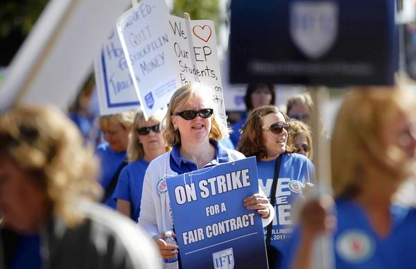 District 124 teachers and support staff employees walk a picket line Tuesday near Central Junior High School in Evergreen Park.