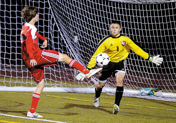 Linganore's Nick Butler fires a shot wide as North Hagerstown goalkeeper Max Ober (1) charges out to defend during Tuesday night's boys soccer game at Mike Callas Stadium.