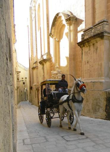 A carriage navigates the narrow streets of Mdina, a city built by Normans.
