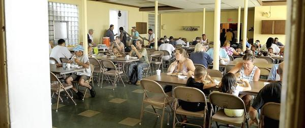 People eat lunch at the ecumenical kitchen at Our Lady of Mount Carmel Church in Allentown.