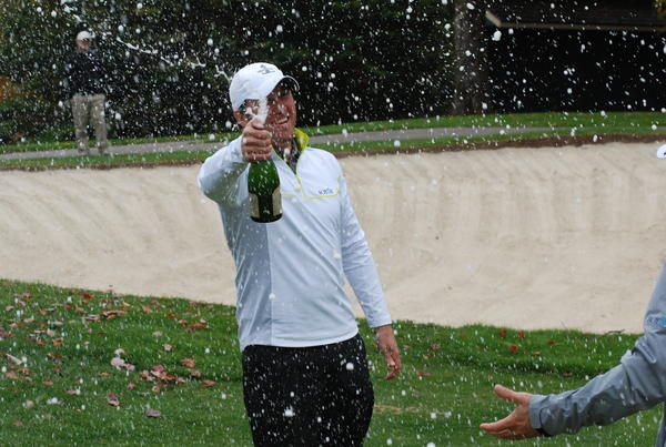 Team Boyne captain Josh Richter uncorks a bottle of champagne moments following Team Boyne's win Tuesday at the Harbor Cup at Boyne Highlands in Harbor Springs. Team Boyne defeated Team Harbor, 18-6.