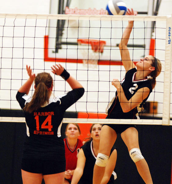 East Jordan's Valerie Peters (right) spikes the ball as Harbor Springs' Abi Coulter (14) goes up for the block during Tuesday's Lake Michigan Conference match at the Harbor Springs High School gym.