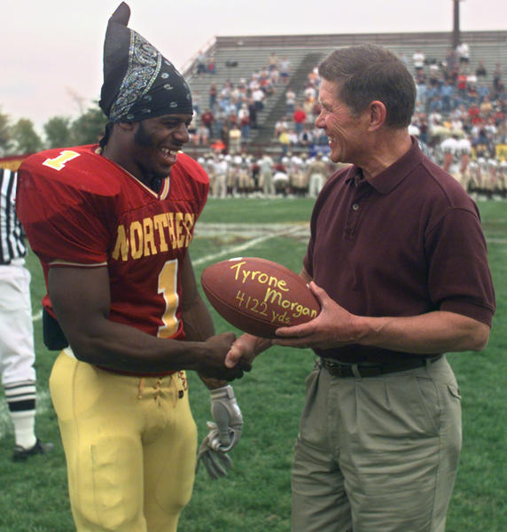 Northern State University's Tyrone Morgan, left, accepts a football from Jim Kretchman in recognition of Morgan's setting a new career rushing mark of 4,122 yards eclipsing Kretchman's record of 4,121 in ceremonies held before Saturday's game at Swisher Field. Morgan added to the total in NSU's win over Southwest State University. photo byjohn davis taken 9/30/2000