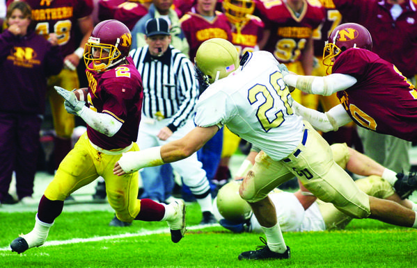 Northern State University's Deacon Burns tries to turn the corner past Concordia University-St. Paul's Reed Tietz as NSU's Charlie Johnston tries to block Tietz, right, during the first half of Saturday's game at Swisher Field.