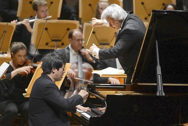 Carl St.Clair conducts the Pacific Symphony as Lang Lang performs on the piano at the Renee and Henry Segerstrom Concert Hall in Costa Mesa.
