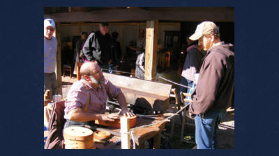 Bob Fike of Glenville shows Rory Mullennex of Bluefield, Va., how thin strips of cherry and walnut are steamed then bent around forms to create wooden boxes, at 2011 Springs Folk Festival.