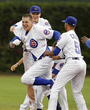 Bryan LaHair of the Cubs is mobbed by teammates after hitting a game-winning one-run single at Wrigley Field.