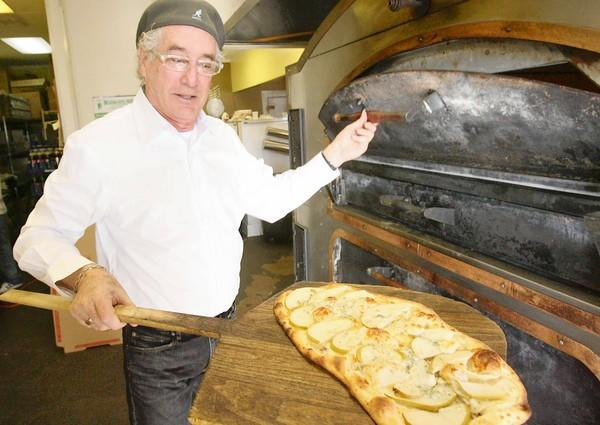 ZPizza founder Sid Fanarof pulls a pizza out of the oven at ZPizza in Laguna Beach in 2009. The location will close Tuesday.