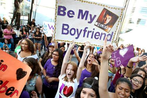 "Justin Bieber fans including Amelia Erichsen, 13, of San Diego, holds a sign reading ""Be My Boyfriend"", before the first of two concerts at Staples Center."
