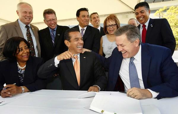 Los Angeles Mayor Antonio Villaraigosa, middle, jokes with AEG President Tim Leiweke, right, as Councilwoman Jan Perry, left, looks on during the signing of agreements to take the next step in landing Los Angeles an NFL team.