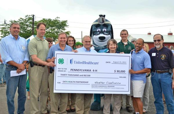 PA check presentation: From left: State Rep. Mike Tobash, State Rep. Mark Longietti, 4-H State Council member Tyler Shaw (Dauphin County), State Sen. John Eichelberger, 4-H State Council member Dawn Craft (Cambria County), Agriculture Secretary George Greig, Pennsylvania 4-H Leader Christy Bartley, 4-H youth John Hess (Erie), David Brown of UnitedHealthcare Community Plan of Pennsylvania, and Mike Glazer of Congressman Glenn Thompson's office.