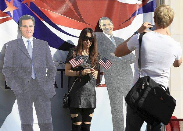 Political enthusiasts in Denver pose for a photo with cutouts of Mitt Romney and President Barack Obama before Wednesday night's debate.