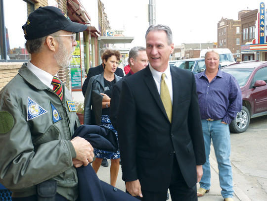 Britton Mayor David Kleinberg, left, leads Gov. Dennis Daugaard and others on a walking tour of downtown Britton Wednesday morning. Britton served as South Dakota's Capital for a Day.  American News Photo by Scott Waltman