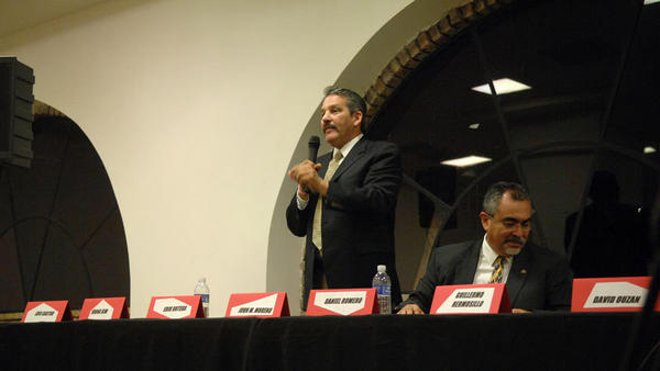 John M. Moreno gives a speech as Daniel Moreno listens at the Calexico City Council candidates forum Wednesday night in Calexico.