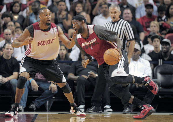 Miami Heat forward LeBron James drives on Rashard Lewis during the Heat's Red and White game.