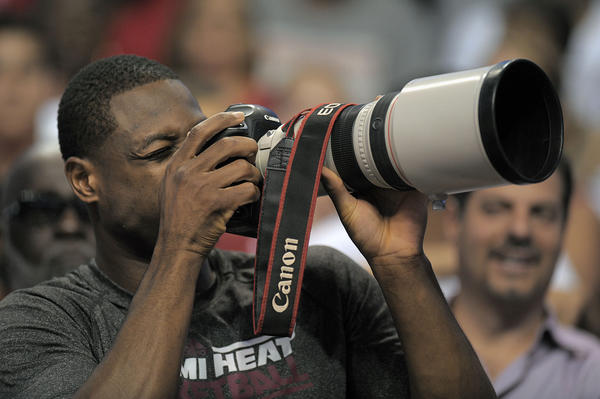 Miami Heat guard Dwyane Wade points a camera at the fans during the Heat's Red and White game.