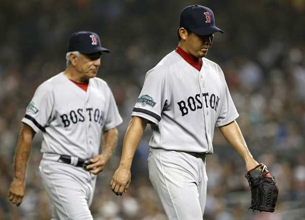 Red Sox starting pitcher Daisuke Matsuzaka (R) walks to the dugout in front of manager Bobby Valentine after being taken out of the game against the New York Yankees during the third inning of their MLB American League baseball game at Yankee Stadium in New York, October 3, 2012.