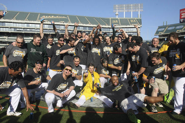 The Oakland Athletics celebrate on the pitcher's mound after winning the AL West title.