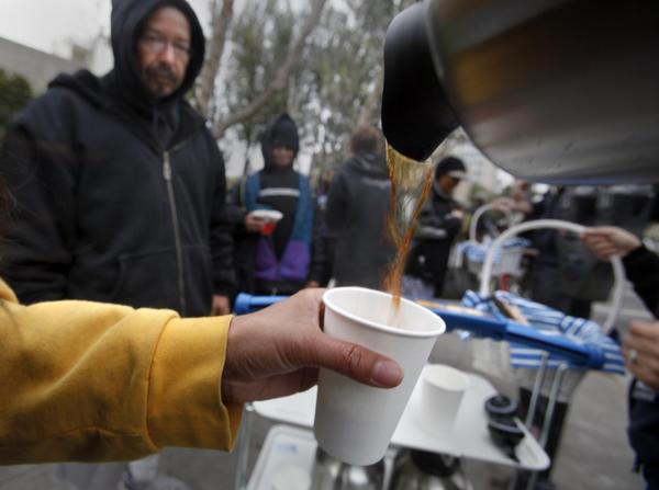 Staff members from the IKEA store in Costa Mesa pour and distribute free cups of coffee to the homeless.