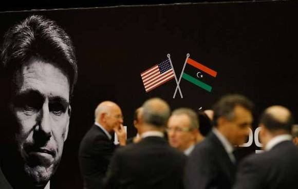 Diplomats and officials gather in front of a picture of slain U.S. ambassador to Libya Stevens during a memorial for Stevens in Tripoli