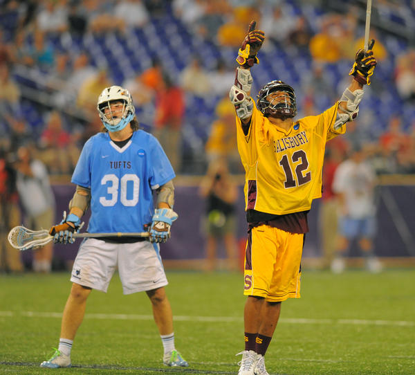 As Tufts midfielder Sam Diss shows his disappointment, Salisbury's Sam Bradman celebrates his seventh goal of the 2011 Division III championship game at M&T Bank Stadium. The Sea Gulls defeated the Jumbos, 19-7.