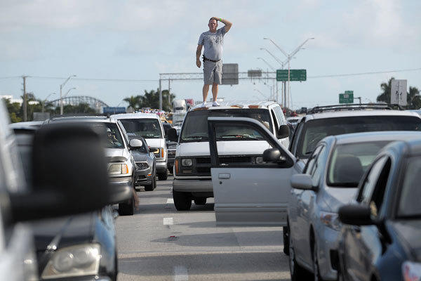 Mark Redner, from Boca Raton, stands on top of his van to see if he can see why traffic on northbound I-95 came to a stop.
