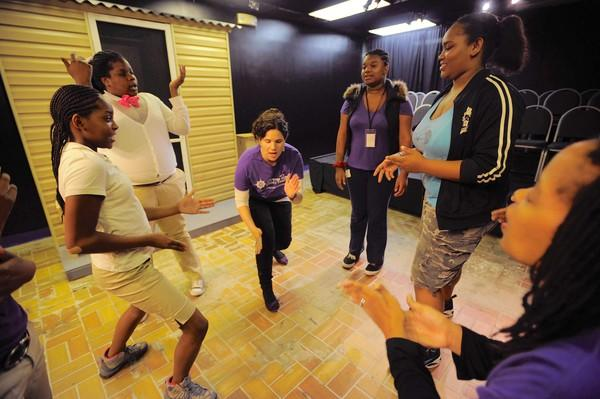 Teaching artists Liza Skinner (center) and Lynne Childress (extreme right) lead a Seeds 4 Success class to mimic poses made by each of them in a get-to-know session at Compass Rose Studio Theater.