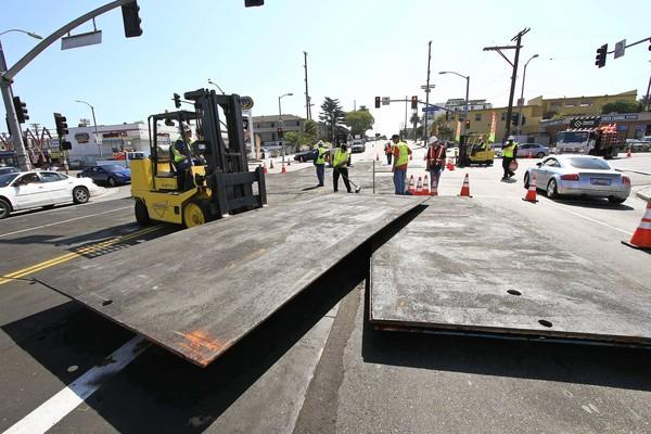Workers lay metal plates at Crenshaw Boulevard and Florence Avenue in preparation for the space shuttle Endeavour's passage through the area en route to the California Science Center.