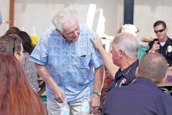 Roger Neth, 85, standing, joins chief Tom Gazsi at the table during the Costa Mesa Public Safety Recognition Barbecue at the Orange County Fairgrounds on Thursday. Neth is Costa Mesa's first sworn police officer and its second chief.
