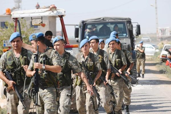 Turkish soldiers move into position in the southern border town of Akcakale, across from Tal Abyad in Syria.