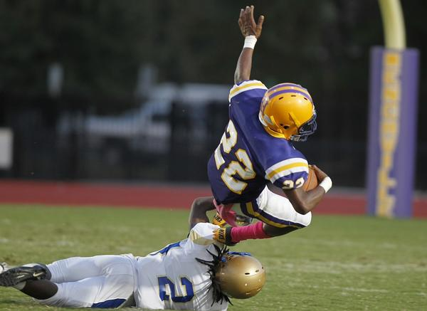 Menchville's Quaret Hilbert is stopped by Phoebus's Robbie Robinson during the second quarter of Thursday's game.