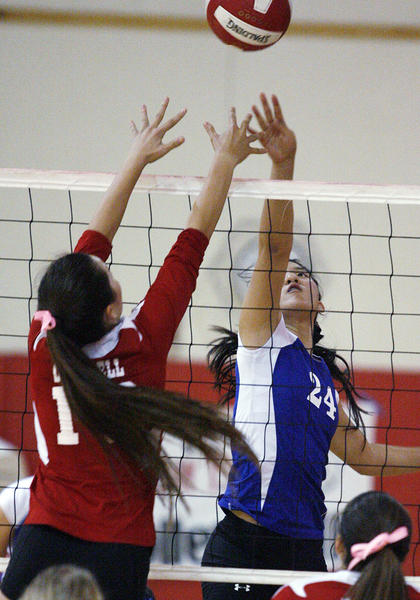 Burbank's Sharon Youn (24) and Burroughs Caitlin Cottrell battle for control of the ball at the net in a rival Pacific League girls volleyball match at Burroughs High School in Burbank on Thursday, October 4, 2012.