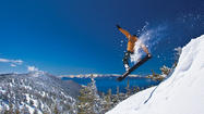 A snowboarder takes to the air with Lake Tahoe in the background