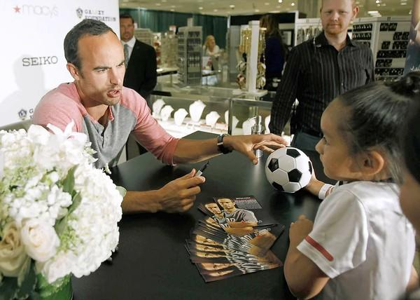 Landon Donovan, left, of the L.A. Galaxy, signs six-year-old Leslie Santiago's mini soccer ball during a special visit at Macy's South Coast Plaza on Thursday.