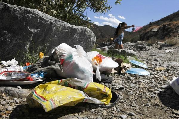 Trash fouls the banks of the East Fork of the San Gabriel River in the Angeles National Forest.