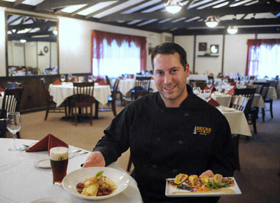 Cale Beck , Executive Chef at Beck's Land and Sea House and part owner with his parents, Randy and Cheryl Beck, holds sauteed pierogies with carmelized onion and smoked sausage and Bavarian eggroll filled with Bratwurst, smoked cheddar cheese and cabbage.