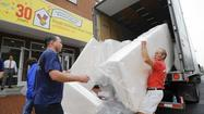 Volunteers move mounds of mattresses