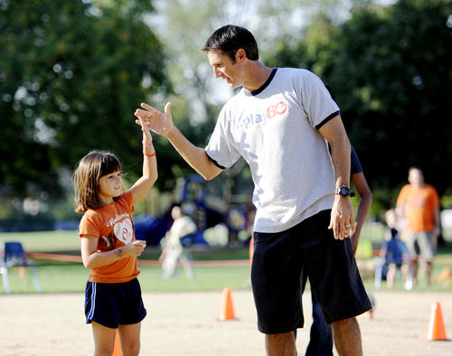 Katie Dausch, 5, a kindergartener at Lutherville Lab, gets a high five from former Ravens kicker Matt Stover at the school's annual Fallfest Friday.