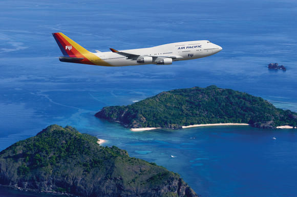 An Air Pacific 747 soars gracefully above the islands