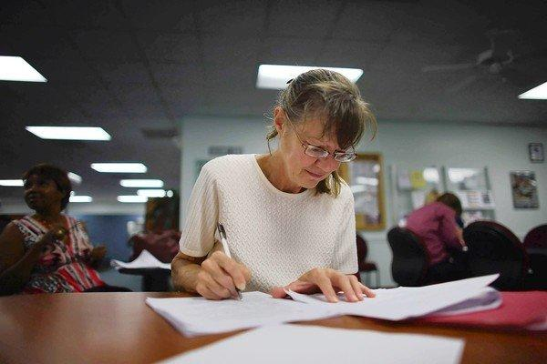 Gloria Richter, at an employment center in Hollywood, Fla., fills out a job application for the bell-ringing openings at the Salvation Army. The Labor Department announced that the U.S. had gained 114,000 jobs in September and that the jobless rate fell from 8.1% to 7.8%.