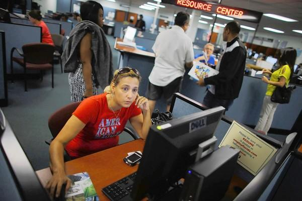 Frances Diaz uses a computer at a job center in Hollywood, Fla., to look for work as a registered nurse.
