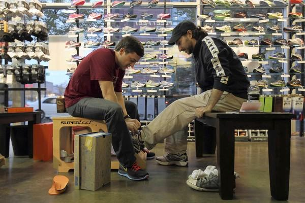 Jason Wells, left, fits Grant Gilb of Riverside for new running shoes at Fleet Feet in Elmhurst. Podiatrists will study possible links between ill-fitting shoes and running injuries by quizzing runners who visit the podiatry tent Sunday at the Chicago Marathon.