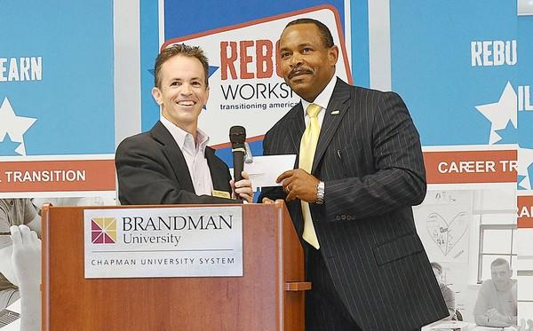 Todd Hanson, left, vice president of Donor and Community Engagement, hands a check for $100,000 to Maurice Wilson, president and executive director of Reboot at Reboot's Class 37's graduation ceremony at Brandman University in Irvine on Friday.