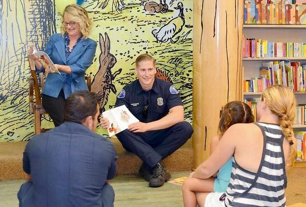 "Katrina Foley, a Newport-Mesa schoolboard trustee, and Aaron Davis, a Costa Mesa firefighter, read aloud ""Ladybug Girl and the Bug Squad"" by David Soman and Jacky Davis to kids for THINK Together's effort to promote literacy in youth and break a world reading record on Thursday at Barnes & Noble at Metro Pointe in Costa Mesa."