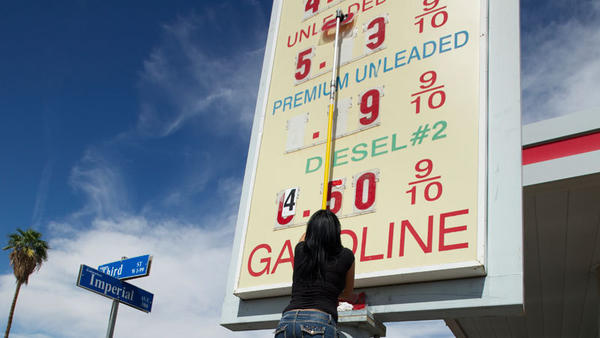 Blanca Palacios changes prices of a gas station in Calexico on Friday. Gas prices have increased dramatically this week.