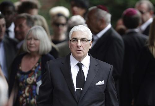 Amy's father, Mitch Winehouse, walks among fellow mourners at the funeral.