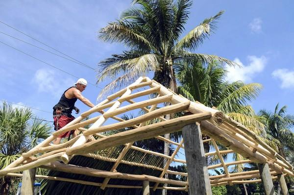 fl-tiki-huts-e, Palm Beach Gardens, 10/5/12 -- Mickey Pettitt of Florida Tiki Huts works on the roof of a backyard tiki hut he is building for a Palm Beach County customer. Mark Randall, South Florida Sun Sentinel