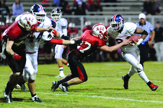 George Rogers Clark linebacker Wesley Wattenburger (27) tries to bring down Lafayette running back  Kylan Nelson 23, while being held by an a Lafayette blocker in the first half.