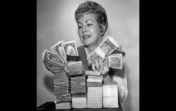 December 1963: Mrs. Joe Melton, teller at Security First National Bank in Fulton-Riverside, holds money illustrating the median income of San Fernando Valley families: $8,736.