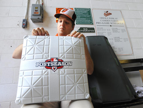 Rob Doetsch,) a member of the tarp crew at Camden Yards, places base jewels on the side of the bases that will be used in the two games against the Yankees. Oriole Park at Camden Yards prepares for the MLB American League Divisional Series as the Baltimore Orioles will face the New York Yankees.